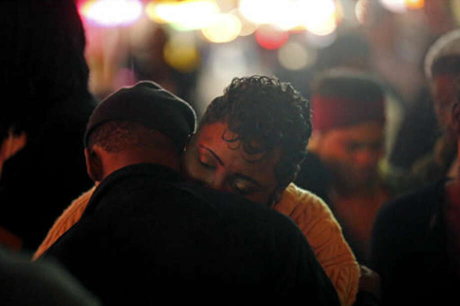 Mezell Gage, who says she raised Demontris Toliver, hugs a fellow mourner at a vigil at Bourbon Street and Iberville Street for Toliver, who was killed in a shooting in the early morning, in the French Quarter section of New Orleans, Sunday, Nov. 27, 2016. Police had already increased patrols in New Orleans' bustling French Quarter before gunfire erupted early Sunday, leaving at least one man dead and several other people wounded in the tourist district known for its bars, bright lights and live music. (AP Photo/Gerald Herbert) Photo: Gerald Herbert