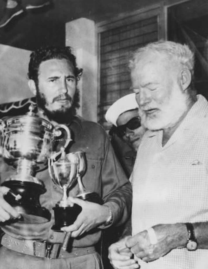 FILE - In this May 15, 1960 file photo, American novelist Ernest Hemingway, right, stands with Cuba's leader Fidel Castro who holds a trophy after winning the individual championship in the annual Hemingway Fishing Tournament in Havana, Cuba. For many artists, Fidel Castro was a contradiction they never quite resolved, a man equally hard to embrace or to ignore. He was the bold revolutionary who defied the U.S. government and inspired the left worldwide and the long-winded despot who reminded them of the right-wing leaders they had traditionally opposed. (AP Photo/File) Photo: STR