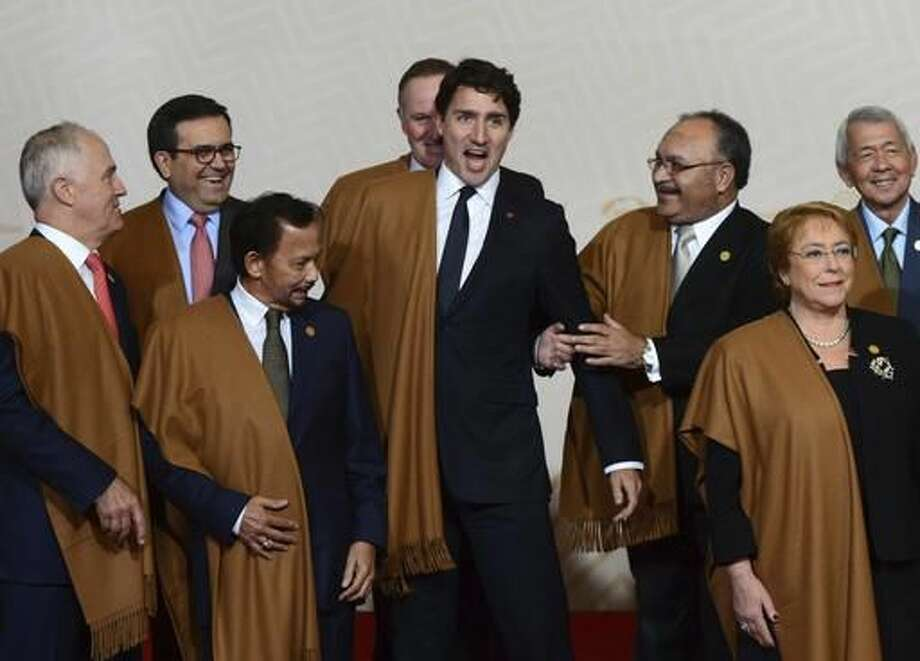 """Canada's Prime Minister Justin Trudeau jokes around with fellow leaders during the group photo at the annual Asia Pacific Economic Cooperation, APEC, summit in Lima, Peru, Sunday, Nov. 20, 2016. The APEC forum closed with a joint pledge to work toward a sweeping new free trade agreement that would include all 21 members as a path """"sustainable, balanced and inclusive growth,"""" despite the political climate. (Sean Kilpatrick /The Canadian Press via AP) Photo: Sean Kilpatrick"""
