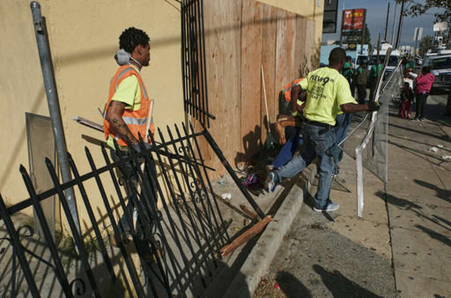 Workers clean debris from an apartment after a car crash in south Los Angeles on Thursday, Dec. 1, 2016. A little boy died when a car crashed into the apartment building. A fire department spokesman said, four others in the unit and the driver were injured in the crash early Thursday. (AP Photo/Richard Vogel) Photo: Richard Vogel
