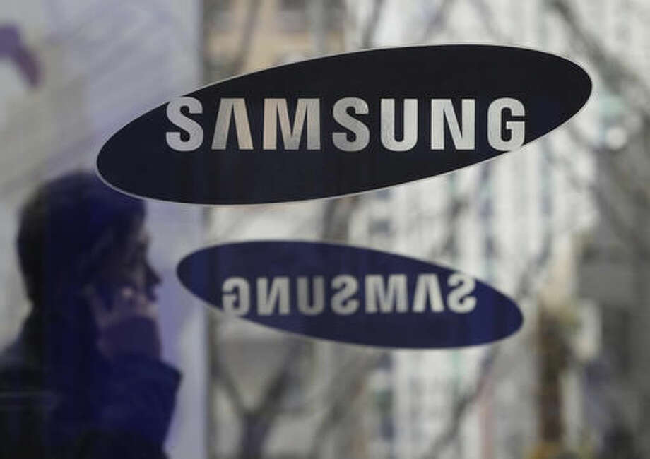 File - In this Dec. 12, 2013 file photo, a man with a mobile phone walks by the Samsung Electronics logos at its headquarters in Seoul, South Korea. Samsung Electronics said Monday, Nov. 14, 2016, it has agreed to acquire auto-systems maker Harman for $8 billion as the South Korean giant eyes the growing market for connected cars. (AP Photo/Ahn Young-joon, File) Photo: Ahn Young-joon