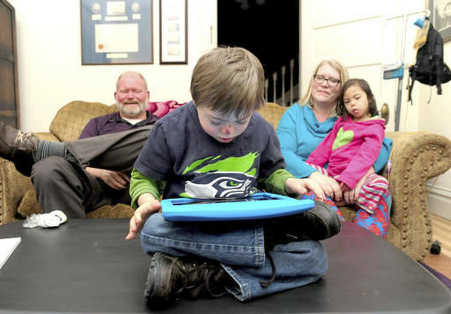 "ADVANCE FOR WEEKEND EDITIONS, DEC. 3-4 - In this Nov. 21. 2016 photo, Leo, 6, watches a video on his iPad while his mom and dad, Matt and Jeni Platte, sit on the couch with his sister, Lily, in Mount Vernon, Wash. Both Leo and Lily are children who have Down syndrome, along with other special needs. ""I never knew I could go to so many doctors appointments,"" Jeni said. ""I think I went to close to 100 this year."" (Brandy Shreve/Skagit Valley Herald via AP) Photo: Brandy Shreve"
