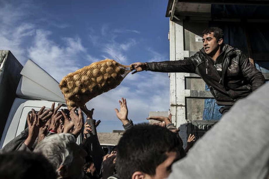 An Iraqi man distributes potatoes to civilians in the Samah district of Mosul, Iraq, Sunday, Dec. 4, 2016. (AP Photo/Manu Brabo) Photo: Manu Brabo