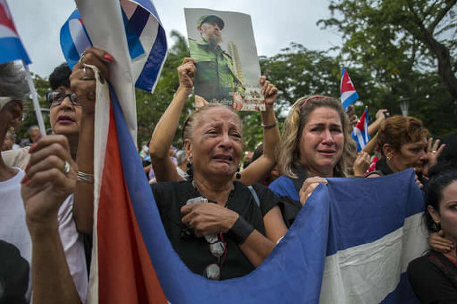 Women weep as the procession carrying the ashes of Cuba's leader Fidel Castro leaves the town of Santa Clara, Cuba, Thursday, Dec. 1, 2016. Castro's ashes are in a four-day journey across Cuba from Havana to their final resting place in the eastern city of Santiago. (AP Photo/Desmond Boylan) Photo: Desmond Boylan