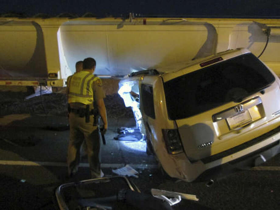 This photo provided by the Arizona Department of Public Safety shows an SUV wedged under a tractor-trailer on the westbound Loop 202 freeway in Chandler, Ariz. on Friday, Dec. 2, 2016. Authorities say a woman survived a three-vehicle accident in which her SUV was involved in two collisions that resulted in her vehicle being wedged until a tractor-trailer. The SUV's top was partially sheared off and firefighters had to extricate the woman.(Arizona Department of Public Safety via AP) Photo: HOGP