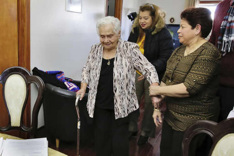 America Maria Hernandez, 99, left, is aided by her granddaughter Monica Martinez, center, and daughter Ana Martinez as she prepares to take the Naturalization Oath of Allegiance, Wednesday, Nov. 23, 2016, in the Queens borough of New York. The Colombian immigrant, who was brought to the U.S. by one of her daughters in 1988, signed her naturalization certificate and took the oath of allegiance in her living room, surrounded by family members and TV cameras. (AP Photo/Richard Drew) Photo: Richard Drew