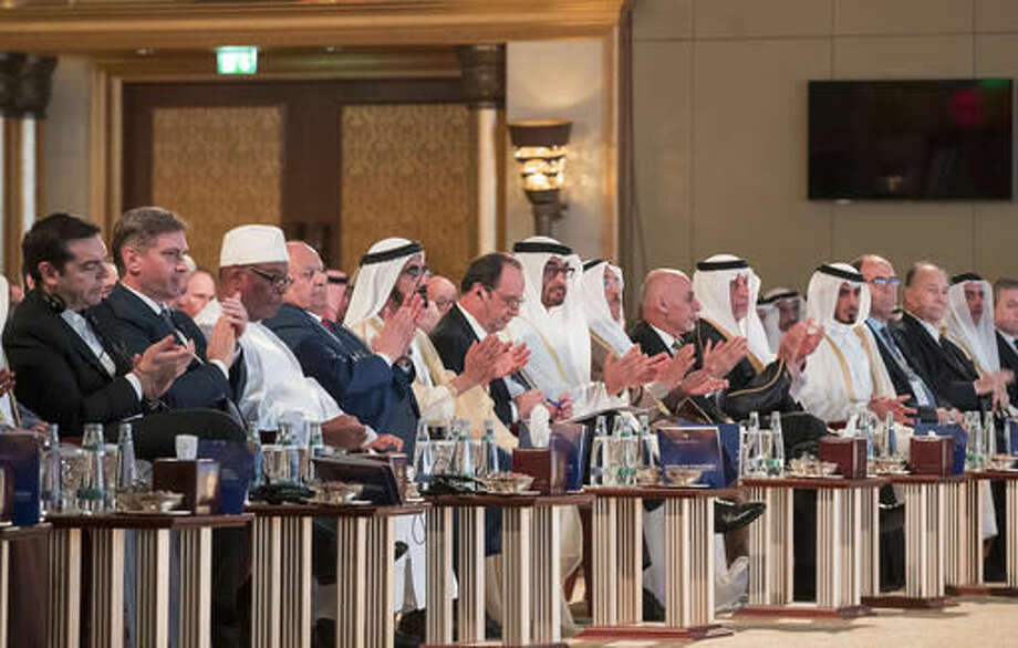 In this Saturday Dec. 3, 2016 photo released by Emirates News Agency, WAM, French President Francois Hollande, centre, takes part between Sheikh Mohammed bin Zayed al-Nahyan, Crown Prince of Abu Dhabi and UAE's deputy commander-in-chief of the armed forces, on his right, and Sheikh Mohammed bin Rashid al-Maktoum, UAE prime minister and ruler of Dubai with the other head of states and dignitaries during the Safeguarding Endangered Cultural Heritage Conference at Emirates Palace in Abu Dhabi, United Arab Emirates. (Emirates News Agency via AP) Photo: Rayan Carter/ Crown Prince Court