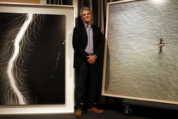 Jeffrey Fraenkel poses for a portrait between two enormous photographs in the shipping and receiving area of his eponymous gallery on November 18, 2014 in San Francisco, Calif. At left is an image by Hiroshi Sugimoto and at right is a Richard Misrach piece.