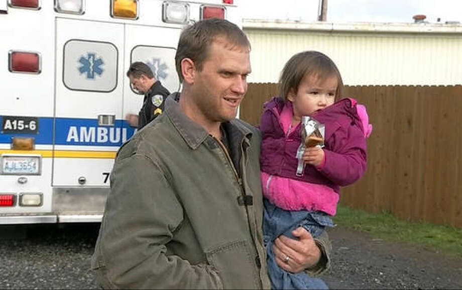 In this image taken from video by KIRO7 photographer Jay Johnson, Jason McAlister holds his daughter at a store Thursday, Nov. 17, 2016, in Matlock, Wash., after they were found safe -- along with McAlister's wife and another of their four children -- earlier Thursday in rural Mason County in Washington state. The couple and the two children were reported missing Tuesday, Nov. 15, 2016, after they went for a drive and failed to pick up their older children after school, authorities said. (@JayOlyKIRO7/KIRO7.com via AP) Photo: Jay Johnson