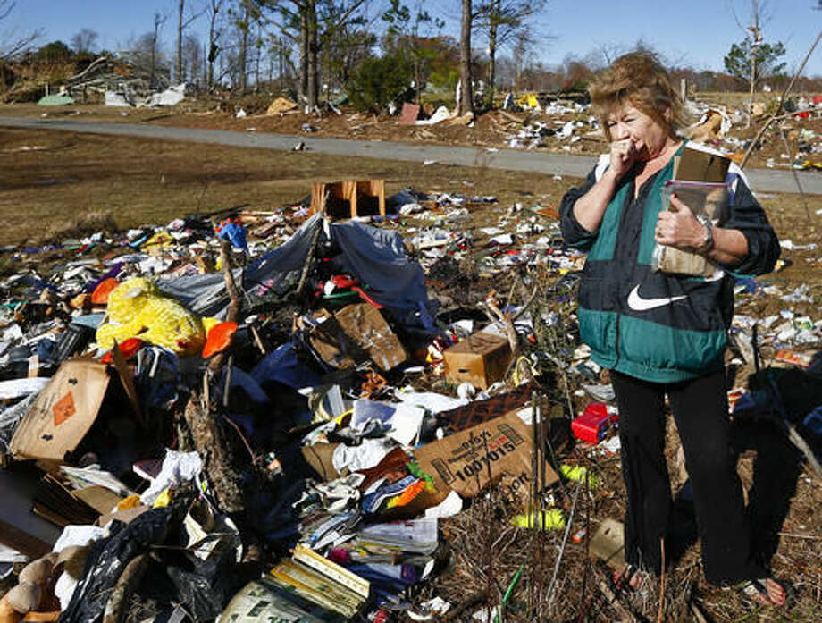 """Marcia Remick, of Rosalie, sniffles after a tear falls from her face after looking through debris Thursday, Dec. 1, 2016, in Rosalie, Ala., the day after a reported tornado struck. Remick holds a bag of photographs and letters she says she is going to try to find the owner of the letters and photographs. """"It's so sad, I really hope I can find the owners, I can't imagine losing family photos and things like that."""" (AP Photo/Brynn Anderson) Photo: Brynn Anderson"""