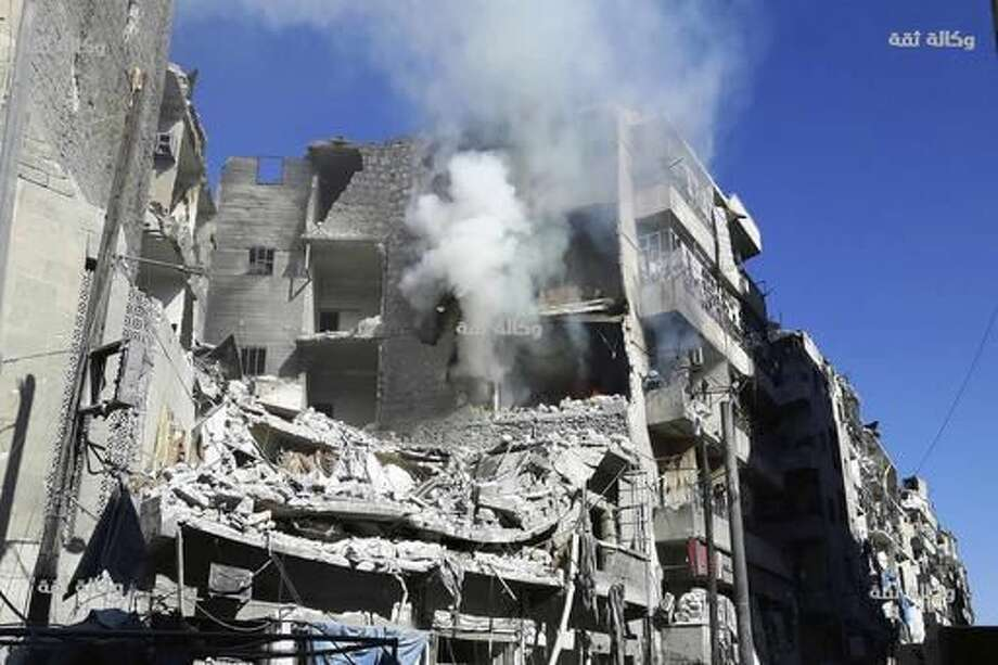 This image released by Thiqa News Agency shows smoke rising and fires still burning after airstrikes hit the Al-Shaar neighborhood of Aleppo, Syria, Friday, Nov. 18, 2016. Intensive bombings pummeled Syria's rebel-held eastern neighborhoods of the city of Aleppo on Friday, residents and rescuers said, hitting an area housing several hospitals and sending the chief of a pediatrics clinic in a frantic search for a place to move his young patients. (Thiqa News via AP) Photo: HONS