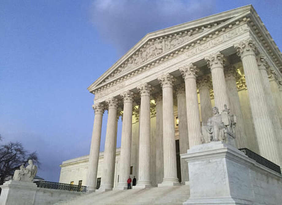 FILE - In this Feb. 13, 2016, file photo, people stand on the steps of the Supreme Court at sunset. The Supreme Court is returning to the familiar intersection of race and politics, in a pair of cases examining redistricting in North Carolina and Virginia. The eight-justice court is hearing arguments Dec. 5, in two cases that deal with the same basic issue of whether race played too large a role in the drawing of electoral districts, to the detriment of African-Americans. (AP Photo/Jon Elswick, file) Photo: Jon Elswick