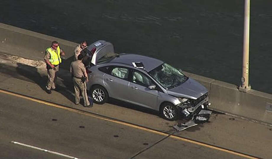 In this image provided by KGO-TV, police look over a car on the Benicia-Martinez left by a woman who jumped from the bridge Monday, Nov. 7, 2016, in Martinez, Calif. Police said a woman purposefully ran over her estranged husband and two of his friends in a crosswalk outside a family court and then jumped to her death off the bridge in the San Francisco Bay Area. (KGO-TV via AP) Photo: HONS
