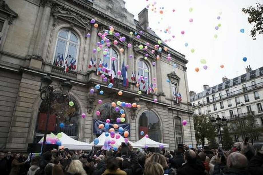 People release balloons outside Paris 11th district town hall, Sunday, Nov. 13, 2016, during a ceremony for the victims of last year's Paris attacks which targeted the Bataclan concert hall as well as a series of bars and killed 130 people. (AP Photo/Kamil Zihnioglu) Photo: Kamil Zihnioglu