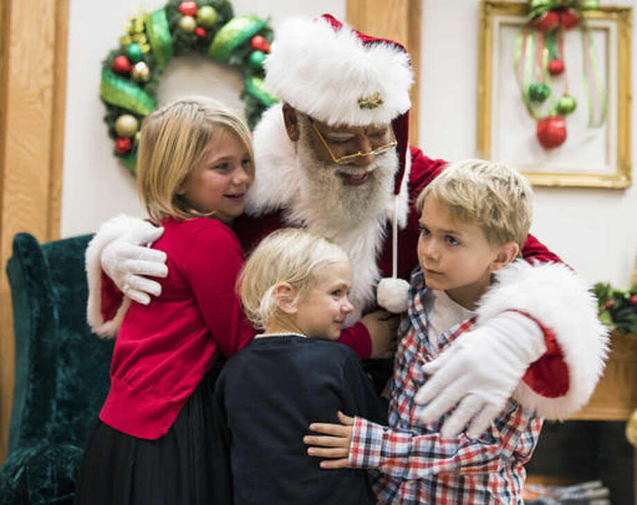 In this Thursday, Dec. 1, 2016 photo, Larry Jefferson, playing the role of Santa, gets a hug from Olivia Major, left, her sister Mallory and brother Preston, of Blaine, at the Santa Experience at Mall of America in Bloomington, Minn. The nation's largest mall is hosting its first-ever black Santa Claus this this weekend. (Leila Navidi/Star Tribune via AP) Photo: Leila Navidi
