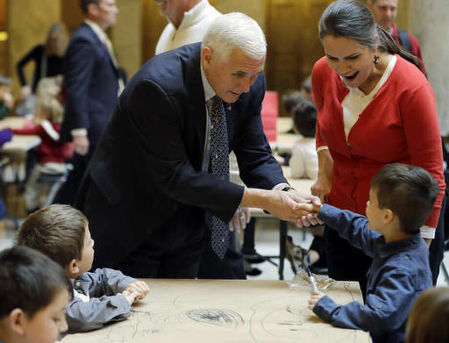 Vice President-elect Mike Pence talks with a young student as they make Christmas tree decorations at the Statehouse Friday, Dec. 2, 2016, in Indianapolis. (AP Photo/Darron Cummings) Photo: Darron Cummings
