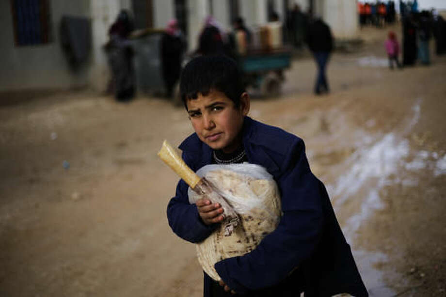A Syrian boy displaced with his family from eastern Aleppo holds a sandwich and bread bag in the village of Jibreen south of Aleppo, Syria, Saturday, Dec. 3, 2016. Aid agencies say that more than 30,000 people have fled rebel-held eastern neighborhoods of Aleppo that have been under tight siege since July. Over the past two weeks, government forces launched an offensive in which they regained control of nearly half areas that had been held by insurgents in their deepest push since the city became contested in July 2012.(AP Photo/Hassan Ammar) Photo: Hassan Ammar