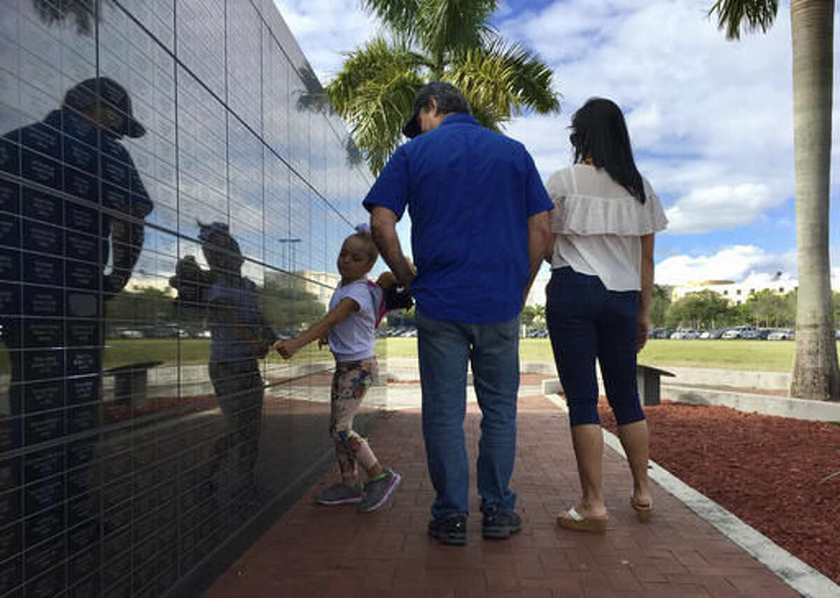 On the same day that Cuba held the funeral for Fidel Castro, dozens of people gathered for a rally, Sunday, Dec. 4, 2016, at the Cuban Memorial in Miami¹s Tamiami Park in honor of people who were victims of Castro's regime and those who died trying to overthrow him. People searched for names of deceased relatives on a black marble wall beneath an obelisk with a Cuban flag pattern. (AP Photo/Adriana Gomez Licon)