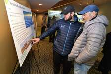 Maritime Rowing Club owner Yan Vengerovskly and his son, Roman, the manager of the club, look over an informational board showing the rehabilitation alternatives to the Walk Bridge replacement.