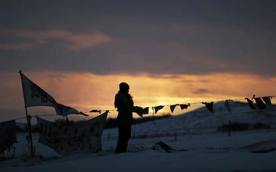 A woman watches the sunset at the Oceti Sakowin camp where people have gathered to protest the Dakota Access oil pipeline in Cannon Ball, N.D., Friday, Dec. 2, 2016. Hundreds of protesters fighting the Dakota Access pipeline have shrugged off the heavy snow, icy winds and frigid temperatures that have swirled around their large encampment. (AP Photo/David Goldman) Photo: David Goldman