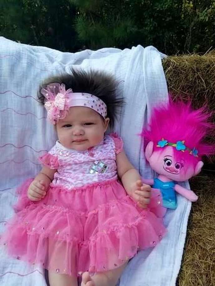 This Nov. 1, 2016 photo provided by Alisha John shows her daughter, Areea John, in Elton, La. John says her 3-month-old daughter has such a full head of hair that strangers stop to admire it, and she dressed the baby as a troll for Halloween. But John tells the American Press that she and her husband, Dakota John, don't have long to play with baby Areea's hair. That's because Dakota John is a member of the Coushatta Indian tribe, which shaves babies' heads as part of a blessing ceremony when they're four months old. (Alisha John via AP) Photo: Alisha John