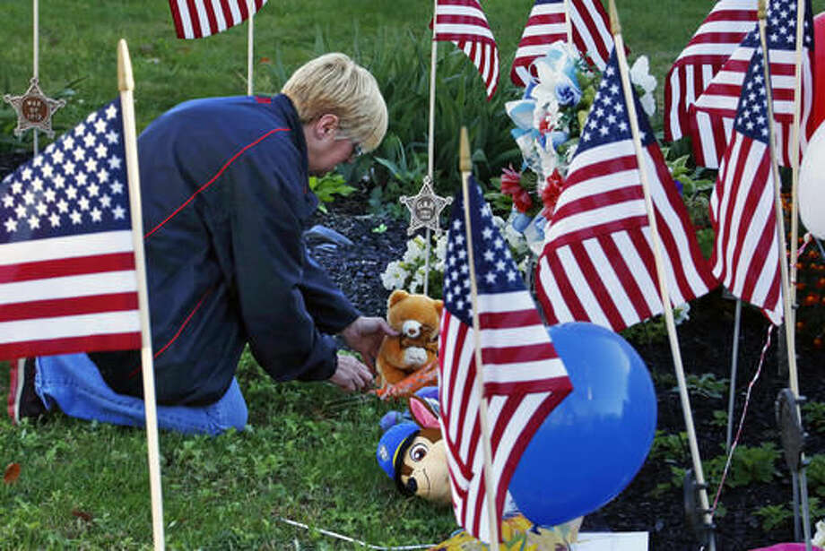 Becky Travaglini, of Canonsburg, Pa., places a teddy bear at a makeshift memorial for the Canonsburg police officers who were shot when they responded to a domestic call early Thursday, Nov 10, 2016, in Canonsburg, Pa. (AP Photo/Gene J. Puskar) Photo: Gene J. Puskar