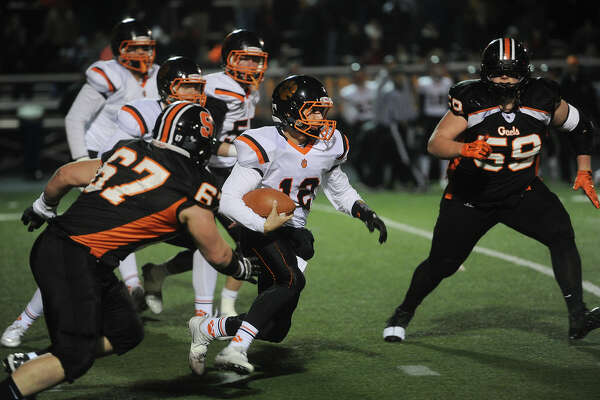 Ridgefield quarterback Drew Fowler runs the ball pursued by Shelton defenders Chris Goodman, left, and Eddie Radzion, right, during the first half of the Class LL football semifinals at Shelton High School in Shelton, Conn. on Monday, December 5, 2016.