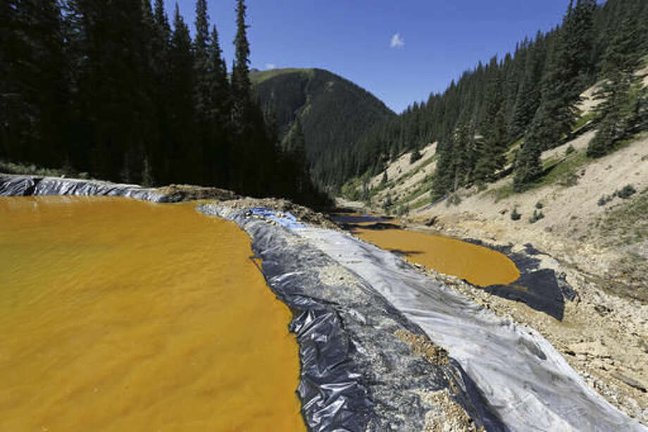 FILE - In this Aug. 14, 2015, file photo, water flows through a series of sediment retention ponds built to reduce heavy metal and chemical contaminants from the Gold King Mine wastewater accident in the spillway about 1/4 mile downstream from the mine outside Silverton, Colo. On Monday, Nov. 28, 2016, the U.S. Supreme Court asked the Justice Department to weigh in on New Mexico's lawsuit against Colorado over the Gold King mine waste spill that polluted rivers in both states and in Utah. (AP Photo/Brennan Linsley, File) Photo: Brennan Linsley