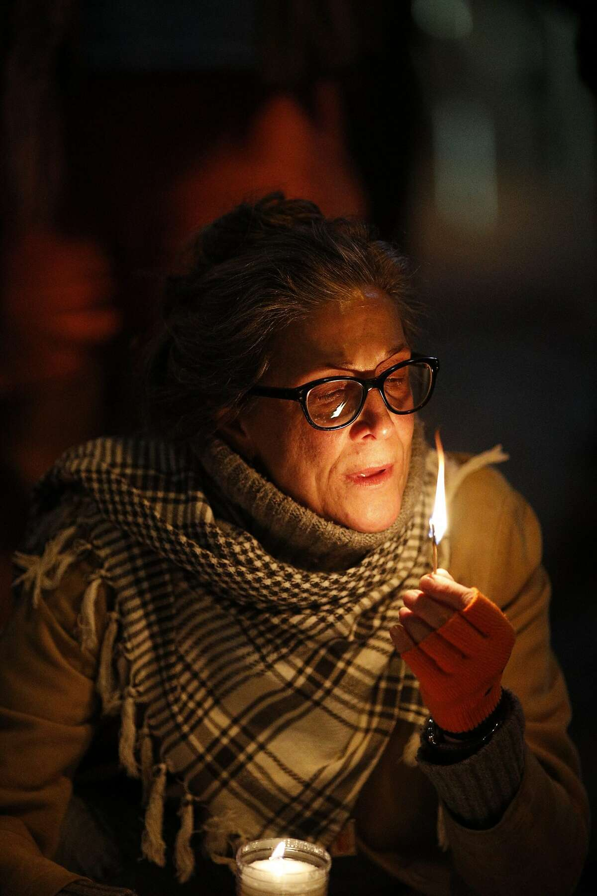 Kimberly Connor's son had a friend who was killed in the fire lights a candle at the vigil for the December 2, 206 Oakland warehouse fire that killed at least 36 people in the San Francisco, CA.