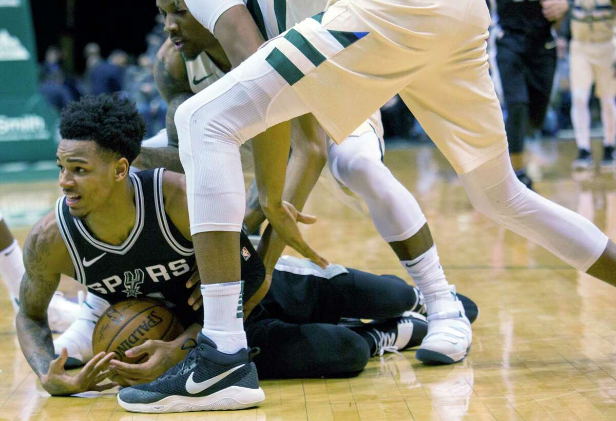 San Antonio Spurs guard Dejounte Murray, left, tries to get a time out called as he battles for the loose ball against the Milwaukee Bucks during the second half of an NBA basketball game Sunday, March 25, 2018, in Milwaukee. (AP Photo/Darren Hauck)