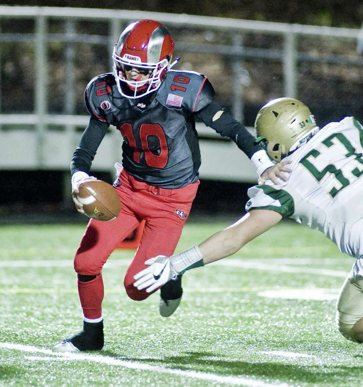 New Canaan High School quarterback Drew Pyne moves out of the reach of Notre Dame-West Haven High School's Justin Keish in the Class L football semifinals at New Canaan. Monday, Dec. 5, 2016