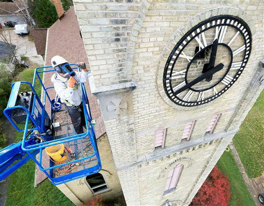 In this Oct. 31, 2016 photo, Kurt Schwarting of Statz Restoration and Engineering, Inc. works on the mortar joints of a clock tower above the Waterloo Historical Society in Waterloo, Wis. Housed in a 1880's-era former church, the museum is working to preserve it's own history through a series of ongoing building improvement efforts. (AP Photo/John Hart, Wisconsin State Journal) Photo: John Hart