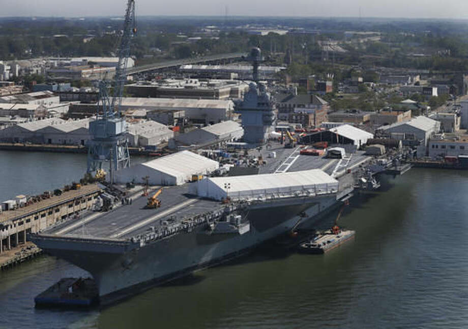 In this April 27, 2016 photo, USS Gerald R. Ford is stationed at Newport News Shipbuilding in Newport News, Va. The $12.9 billion warship, the first of the Navy's next generation of aircraft carriers, is in the final stages of construction after cost overruns and a delay of more than one year. This carrier and those that will follow are being built to replace the Nimitz-class carriers, which were first commissioned in 1975. ( Photo/Steve Helber) Photo: Steve Helber