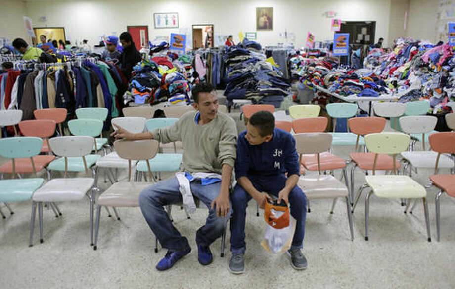 Roger Mesa, right, a 15-year-old from Honduras who is headed to Miami with his father, Luis Carlos, a construction worker, left, sit at the Sacred Heart Community Center in the Rio Grande Valley border city of McAllen, Texas, Sunday, Nov. 13, 2016, after they were released after processing by U.S. Customs and Border Patrol. President-elect Donald Trump is starting to sound a lot more like President Barack Obama on his stance on immigration and easing his pledge to build a wall across the Mexican border. (AP Photo/Eric Gay) Photo: Eric Gay