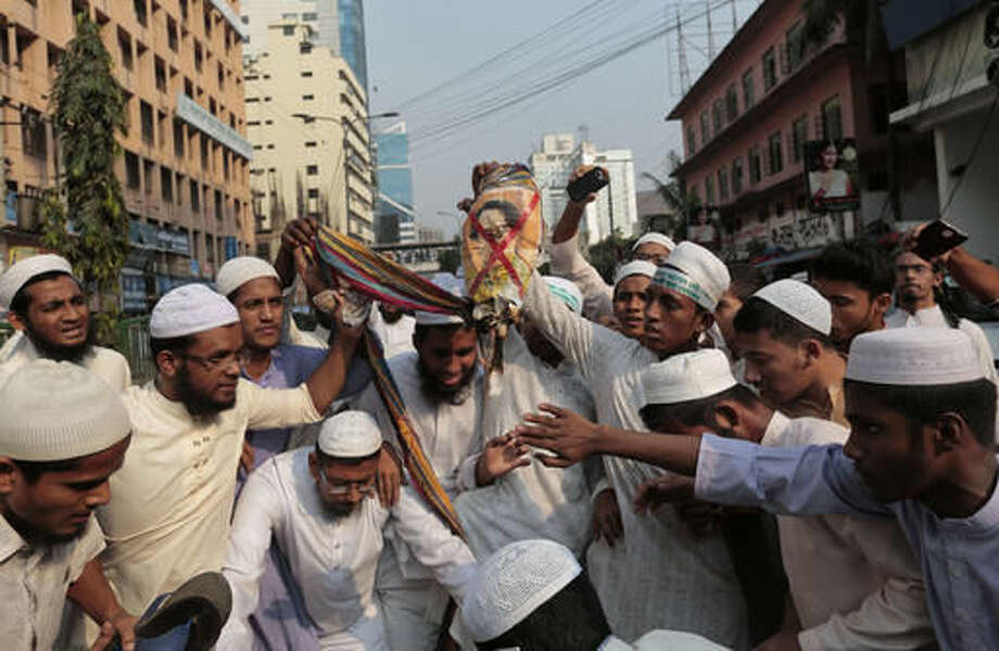"Bangladeshi activists of several Islamic groups burn an effigy of Myanmar's Foreign Minister and Nobel Peace Prize laureate Aung San Suu Kyi during a protest rally against the persecution of Rohingya Muslims in Myanmar, after Friday prayers in Dhaka, Bangladesh, Nov. 25, 2016. Chanting ""Stop killing Rohingya Muslims,"" they marched in Dhaka amid tight security Friday as the violence in Myanmar's Rakhine state escalated, forcing thousands to leave their homes. (AP Photo/A.M. Ahad) Photo: A.M. Ahad"