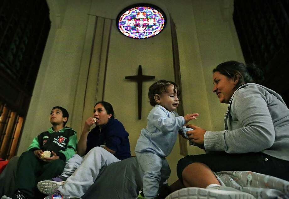 Maria Teresa Quinones, right, plays with her 1 year old son Angel Gael Vanegas from Honduras, as Xiomara Vega Morales, 33 sits with her son Marlon Vega Morales, 8, left, of Guatemala in the sanctuary at the San Antonio Mennonite Church where hundreds of immigrants from Central America have been dropped off by ICE.  Volunteers mentioned they went out to buy blankets and air mattresses, and the last bus dropped off another group at 3 A.M. on Monday, Dec. 5, 2016. Photo: Bob Owen, San Antonio Express-News / ©2016 San Antonio Express-News