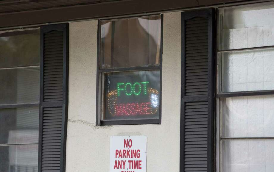 Signs at a massage parlor on Richmond remained lit last month even after the establishment was  sued by Harris County on accusations of being a front for prostitution. Photo: Yi-Chin Lee, Staff / © 2016  Houston Chronicle