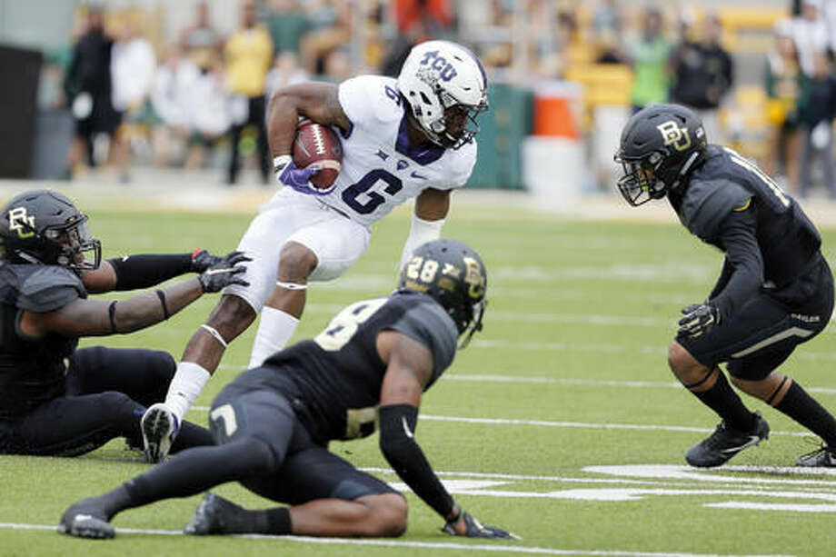 TCU running back Darius Anderson gets by a couple of tackle attempt by Baylor safety Orion Stewart (28) ad others running the ball in the first half of an NCAA college football game, Saturday, Nov. 5, 2016, in Waco, Texas. (AP Photo/Tony Gutierrez) Photo: Tony Gutierrez