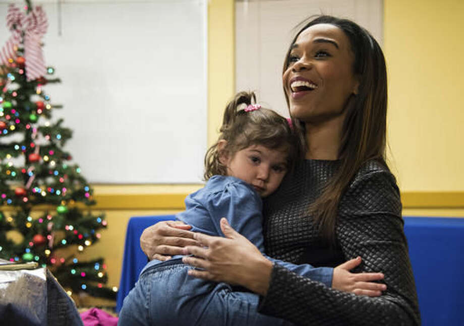 In this Nov. 28, 2016 photo, Auburn High School graduate turned pop-star, Michelle Williams, right, sits with Natalya Tellez, while opening gifts at the Blackhawk Boys and Girls Club in Rockford, Ill. The former Destiny's Child member returned to her hometown Monday to surprise a family in need. Williams surprised the family of eight with clothes, coats and hats for the winter, paid for by the Boys and Girls Clubs of America 12 Days of Giving Program. (Kayli Plotner/Rockford Register Star via AP) Photo: Kayli Plotner