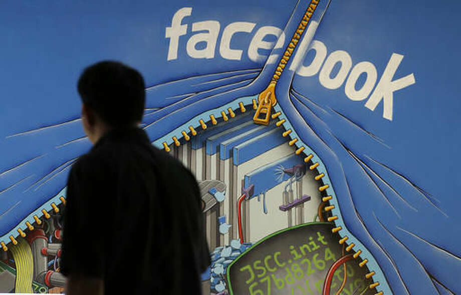 FILE - In this June 11, 2014, file photo, a man walks past a mural in an office on the Facebook campus in Menlo Park, Calif. Some Facebook users received an unsettling shock Friday, Nov. 11, 2016, when an unexplained glitch caused the social networking service to post a notice that implied they were dead. (AP Photo/Jeff Chiu, File) Photo: Jeff Chiu