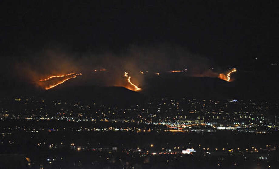 A fire burns on Green Mountain in Lakewood, Colo., Monday, Nov. 28, 2016. Some residents of suburban west Denver have been ordered to evacuate because of the grass fire in the foothills that's visible from miles away. (Katie Wood/The Denver Post via AP) Photo: Katie Wood