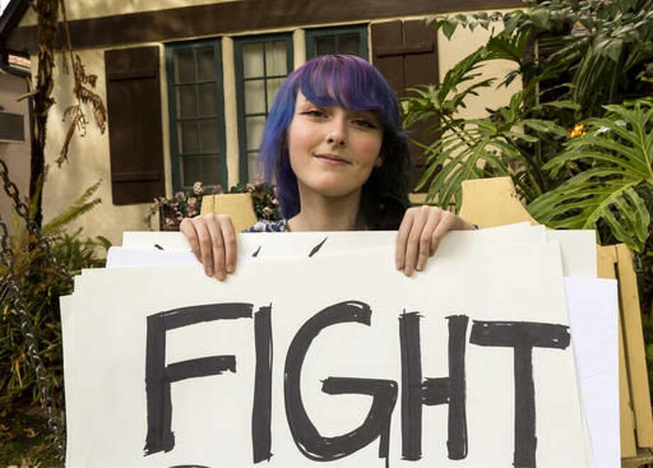 In this Monday, Nov. 21, 2016, photo, high school student Amellia Sones, 14, who helped organize a Ventura Boulevard protest after the presidential election, poses with some of her signs at her home in Los Angeles. (AP Photo/Damian Dovarganes) Photo: Damian Dovarganes