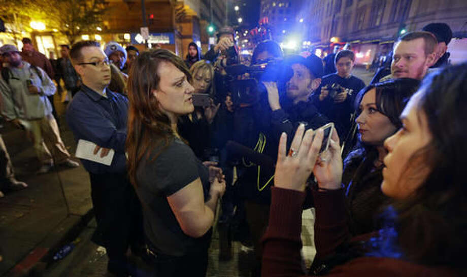 Sharon Keith, center-left, who works in a store near where a shooting took place, Wednesday, Nov. 9, 2016, in downtown Seattle, cries as she talks to reporters about the shooting. Authorities say a man escaped on foot after firing into a crowd and wounding five people outside a convenience store in downtown Seattle. (AP Photo/Ted S. Warren) Photo: Ted S. Warren