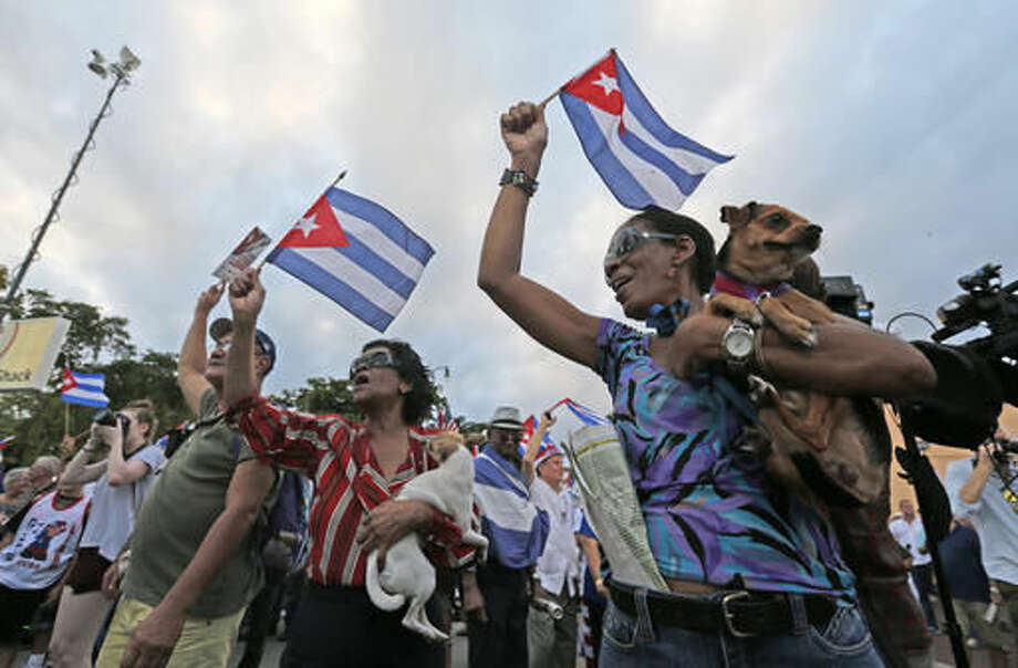 Iris Castillo, right, and her dog Negrito, and Avelina Questa, center, and her dog Chiquitica, dance and wave Cuban flags as they attend a rally, Wednesday, Nov. 30, 2016, in the Little Havana neighborhood of Miami. Hundreds of Cuban exiles in Miami rallied Wednesday for freedom and democracy on the communist island following the death of revolutionary leader Fidel Castro. (AP Photo/Wilfredo Lee) Photo: Wilfredo Lee