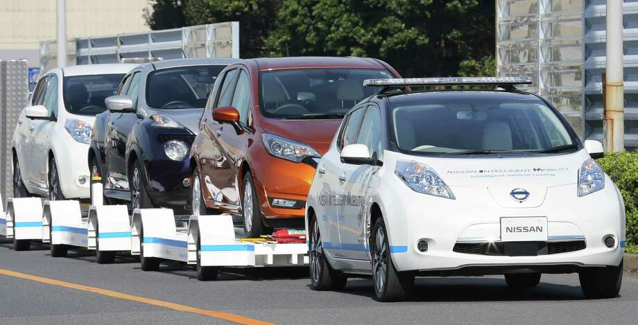 A Nissan Leaf with no one inside pulls a trailer with three other Leafs on it during a demonstration of the automaker's Intelligent Vehicle Towing system at the Nissan Oppama plant in Yokohama. Photo: Koji Sasahara, STF / Copyright 2016 The Associated Press. All rights reserved.