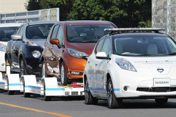 A Nissan Leaf with no one inside pulls a trailer with three other Leafs on it during a demonstration of the automaker's Intelligent Vehicle Towing system at the Nissan Oppama plant in Yokohama.