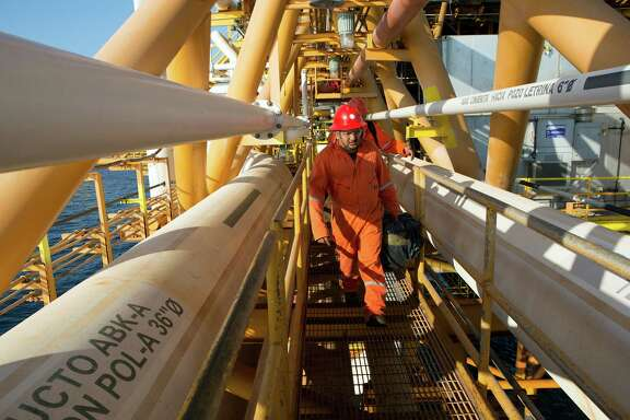 """Workers walk across a connecting bridge on a Pemex platform complex in the Gulf of Mexico off Ciudad del Carmen. A """"farm-out"""" agreement means BHP Billiton will develop a deep-water field known as the Trion block, near Mexico's maritime boundary with the U.S."""