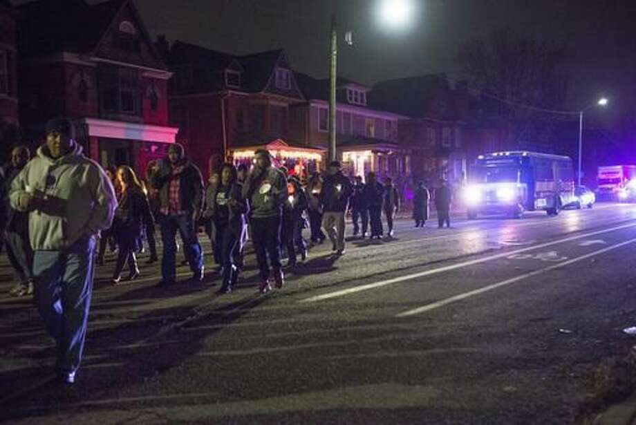 People march in a candlelight vigil and procession in memory of Wayne State University police officer, Collin Rose, around Scripps Park towards the location of the fatal shooting, to pay respect to Rose, in Detroit, Saturday, Nov. 26, 2016. Rose was shot as he tried to arrest DeAngelo Davis, who was arraigned Friday on murder and gun charges. Police say the canine officer was investigating the possible thefts of navigation systems near the campus, and stopped Davis, who was riding a bicycle. (Virginia Lozano/Detroit News via AP) Photo: Virginia Lozano