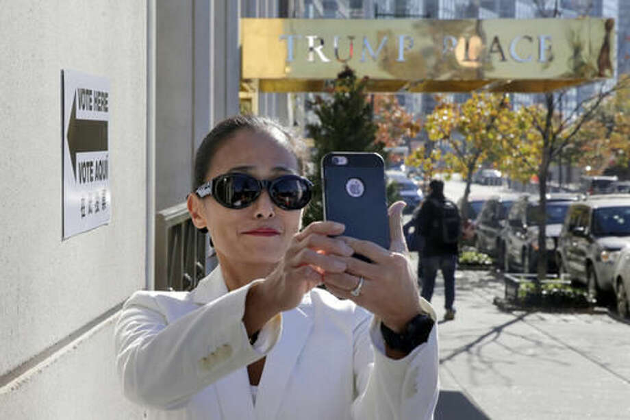 FILE- In this Nov. 8, 2016 file photo, a woman takes a selfie outside a polling place after voting in an apartment building named for Republican presidential candidate Donald Trump in New York. The luxury apartment building is one of three that will have the president-elect's name stripped from it after hundreds of residents signed an online petition demanding it be removed. (AP Photo/Richard Drew) Photo: Richard Drew