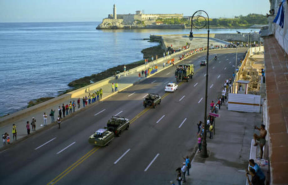 People watch the motorcade transporting the remains of Cuban leader Fidel Castro drive past, along the Malecon seaside boulevard, in Havana, Cuba, Wednesday, Nov. 30, 2016. Castro's ashes have begun a four-day journey across Cuba from Havana to their final resting place in the eastern city of Santiago. (AP Photo/Ramon Espinosa) Photo: Ramon Espinosa